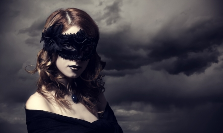Enchantress in mask at storm sky background. photo