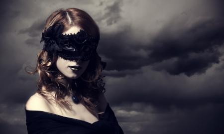 enchantress: Enchantress in mask at storm sky background.