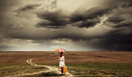 mujer con maleta: Chica con paraguas y la maleta caminando por la carretera en campo.