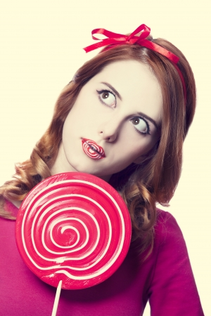 Beautiful redhead girl with lollipop. Stock Photo - 16695897