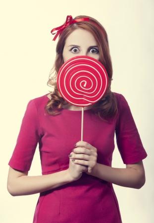 Beautiful redhead girl with lollipop. Stock Photo - 16695903