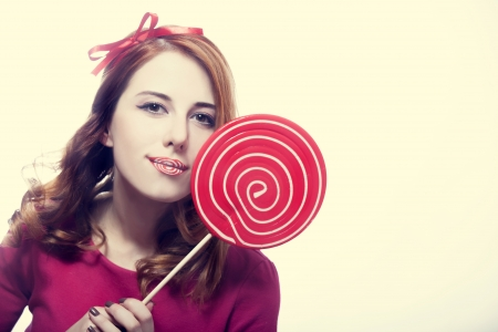 Beautiful redhead girl with lollipop. Photo in retro style. Stock Photo - 16695889