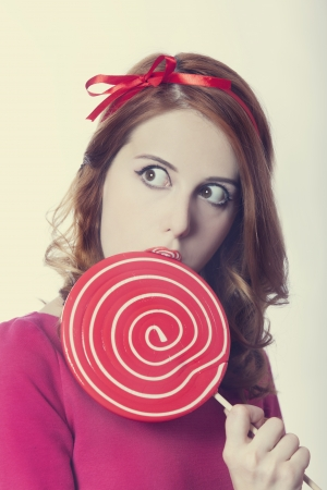 Beautiful redhead girl with lollipop.  photo