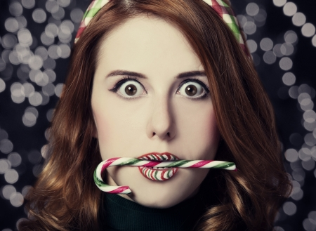 Beautiful surprised women with Christmas candy.  photo