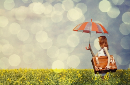 Redhead enchantress with umbrella and suitcase at spring rapeseed field. photo