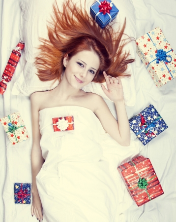 luxuriate: Redhead girl in bed with gifts. Photo in warm tone style.
