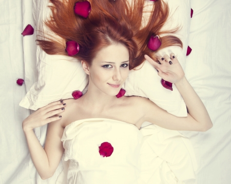 luxuriate: Beautiful red-haired girl in bed with rose petal  Studio shot  Stock Photo