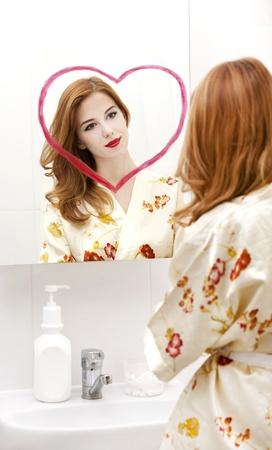 Redhead girl near mirror with heart it in bathroom. Stock Photo - 16824789