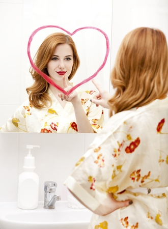 Redhead girl near mirror with heart it in bathroom. Stock Photo - 16824795