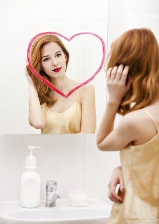 Redhead girl near mirror with heart it in bathroom. Stock Photo - 16824791