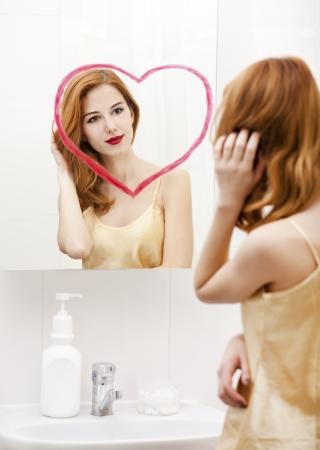 Redhead girl near mirror with heart it in bathroom. Stock Photo - 16824791