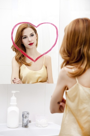 Redhead girl near mirror with heart it in bathroom. Stock Photo - 16824803