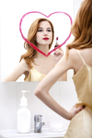 Redhead girl near mirror with heart it in bathroom. Stock Photo - 16824777