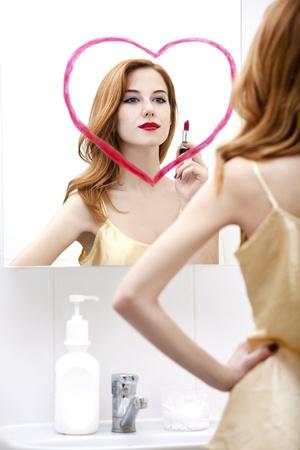 Redhead girl near mirror with heart it in bathroom. Stock Photo - 16824777