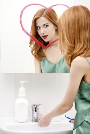 Redhead girl near mirror with heart it in bathroom. Stock Photo - 16824797