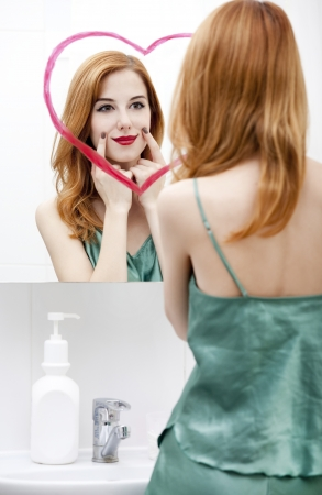 Redhead girl near mirror with heart it in bathroom. Stock Photo - 16824762