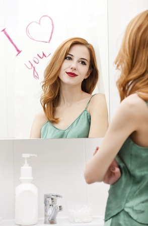 Redhead girl near mirror with heart it in bathroom. photo