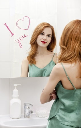 Redhead girl near mirror with heart it in bathroom. Stock Photo - 16824802