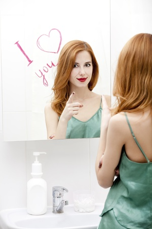 Redhead girl near mirror with heart it in bathroom. Stock Photo - 16824783