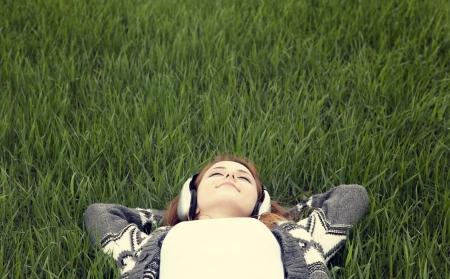 Young with headphones lying down at green grass. photo