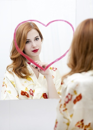 Redhead girl near mirror with heart it in bathroom. Stock Photo - 16824759
