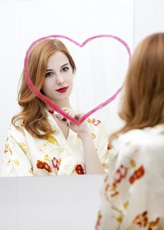 Redhead girl near mirror with heart it in bathroom. Stock Photo - 16824759