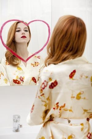 Redhead girl near mirror with heart it in bathroom. Stock Photo - 16824761