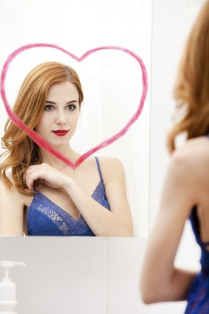 Redhead girl near mirror with heart it in bathroom. Stock Photo - 16824779