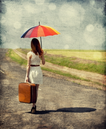 Young fashion girl with umbrella and suitcase at spring outdoor. Photo with retro bokeh at background. photo