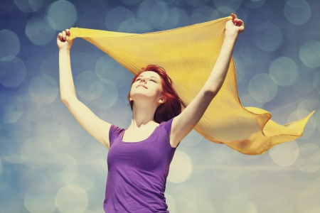 Young woman with open arms keep yellow silk on wind. Photo with bokeh at background. Stock Photo - 16829944