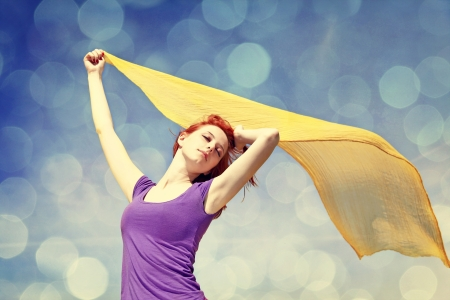 Young woman with open arms keep yellow silk on wind. Photo with bokeh at background. Stock Photo - 16829947