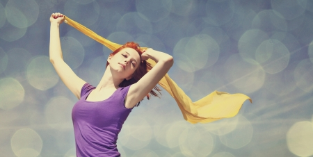 Young woman with open arms keep yellow silk on wind. Photo with bokeh at background. Stock Photo - 16829937