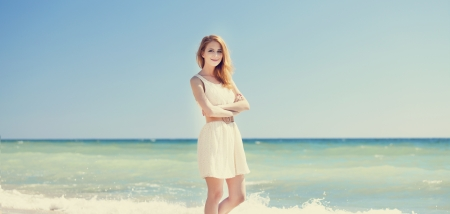 Young redhead girl at the beach. photo