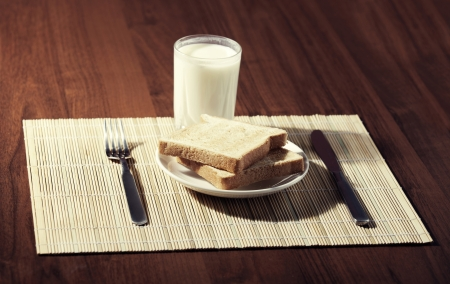 Toast with a glass of milk and knife on wooden background photo