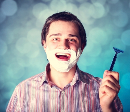 Man shaving isolated on blue background photo