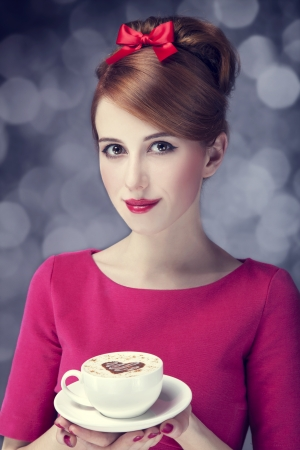 Redhead girl with coffee cup. St. Valentines Day.