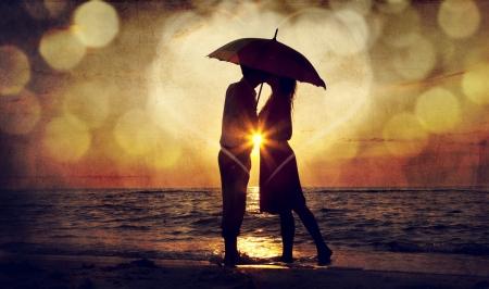 romance: Pares que beijam sob guarda-sol na praia, no pôr do sol. Foto no estilo imagem antiga.