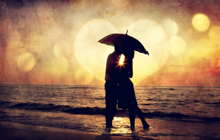 Couple kissing under umbrella at the beach in sunset. Photo in old image style. Stock Photo