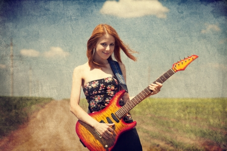 Red-head girl with guitar. Photo in old image style. Stock fotó