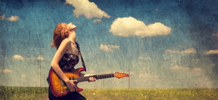 Red-head girl with guitar. Photo in old image style. photo