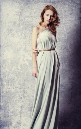 Beautiful woman posing in a long dress photo