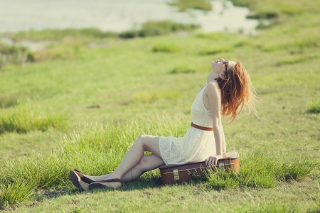 Young fashion girl with suitcase sitting at spring grass near lake. photo