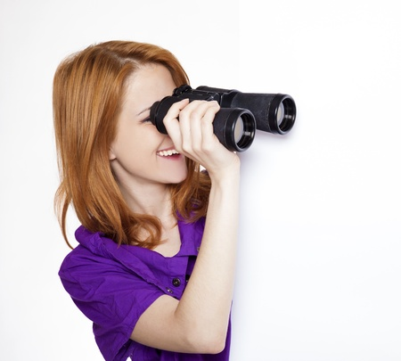 shyness: Teen red-haired girl with binoculars isolated on white background