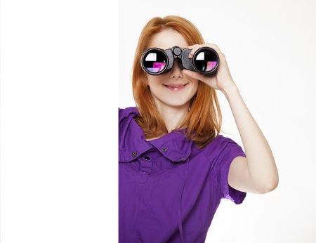 Teen red-haired girl with binoculars isolated on white background photo
