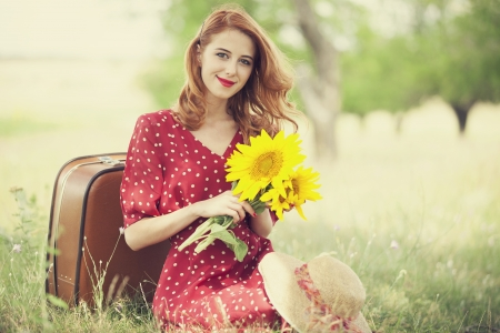 girl in red dress: Redhead girl with sunflower at outdoor.