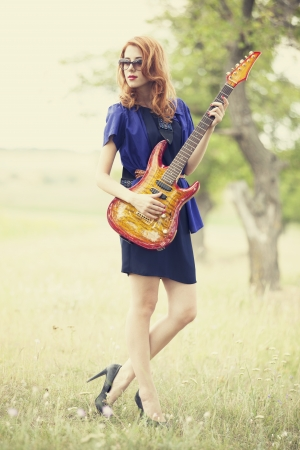 Style redhead girl with guitar at outdoor. Stock Photo - 17602520