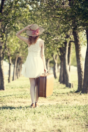Redhead girl with suitcase at trees alley. Stock Photo