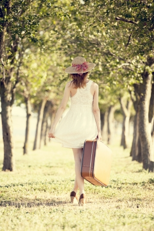 Redhead girl with suitcase at tree's alley. Stock Photo - 17602532