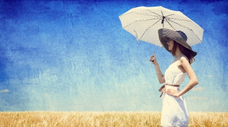 Women with umbrella at wheat field. Photo in old retro style. photo