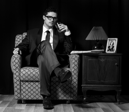 Man with alcohol sitting in vintage armchair photo